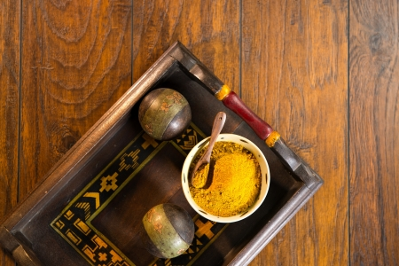 Ceramic bowl filled with yellow curry powder with a wood spoon on a decorative wooden tray. The tray is shot on a wood surface.