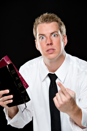 Young man in a white dress shirt and tie, holding 2 bibles in one hand and pointing with his other. His facial expression is quite intense.  This image is shot on a black background using High-key lighting. Stock Photo - 21232983