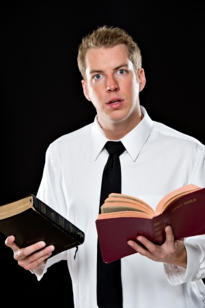 collared shirt: Young man in a shirt and tie, holding 2 bibles. He appears to be in deep thought and is shot on a black background using High-key lighting. Stock Photo