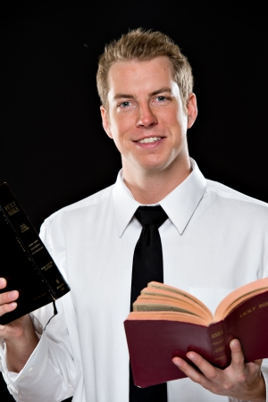hair tie: Smiling young man in a white dress shirt and black tie, holding 2 bibles, shot on a black background using High-key lighting.