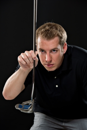 lining up: Portrait of a young male model in golf attire, holding a driver, lining up a shot.