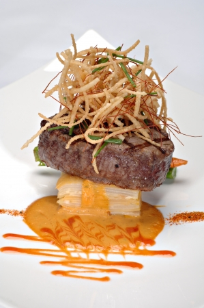 plated: Beautifully plated Grilled Filet Mignon over scalloped potatoes au gratin, topped with deep fried onions.