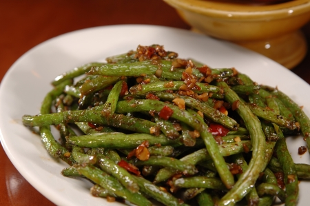 A plate of fresh-cut stir-fried green beans with a red chili sauce. There is a yellow bowl in the background. Imagens