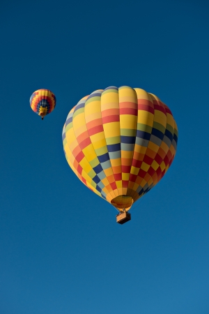 Two hot air balloons just after lift off.  Set against a deep blue sky. 版權商用圖片 - 21907614