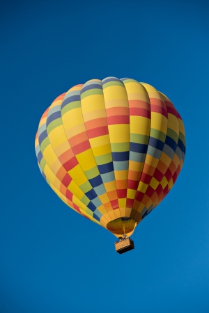 Colorful hot air balloon just after lift off.  Set against a deep blue sky.  版權商用圖片