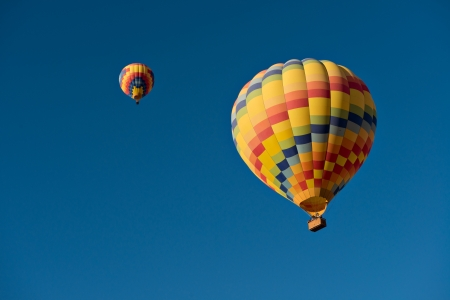 Two hot air balloons just after lift off.  Set against a deep blue sky. 版權商用圖片 - 21907635