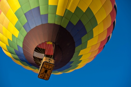 Looking up at a colorful hot air balloon just after lift off.  Set against a deep blue sky. Stock Photo