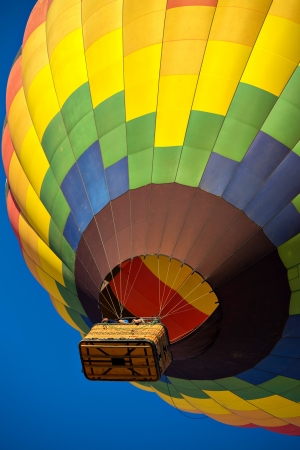Looking up at a colorful hot air balloon just after lift off.  Set against a deep blue sky. 版權商用圖片