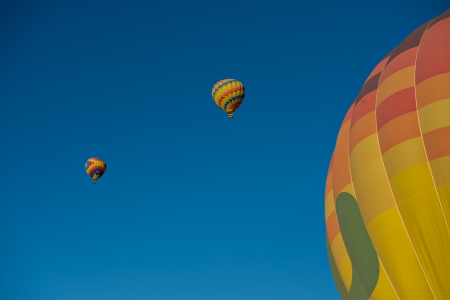 Three hot air balloons just after lift off.  Set against a deep blue sky.