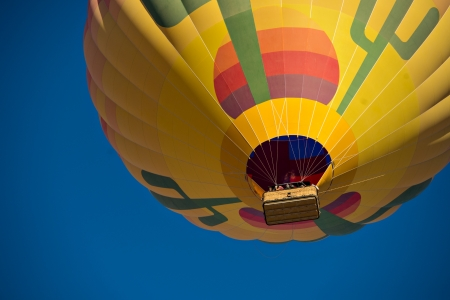 Looking up at a colorful hot air balloon just after lift off.  Set against a deep blue sky. 版權商用圖片 - 21907770