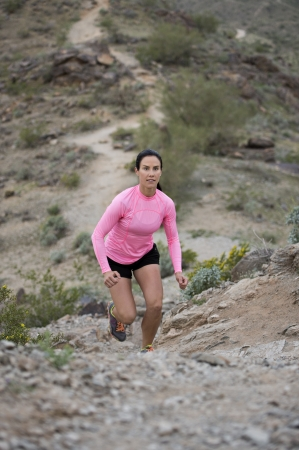 Young woman trail running up a hill outdoors at South Mountain Park in Phoenix, Arizona.