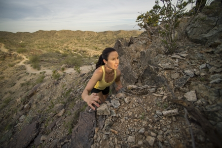 phoenix arizona: Young woman peaking over some boulders off of a trail at South Mountain Park in Phoenix, Arizona.