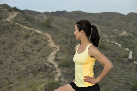 Young woman pauses at the top of a trail midway through her run at South Mountain Park in Phoenix, Arizona. photo