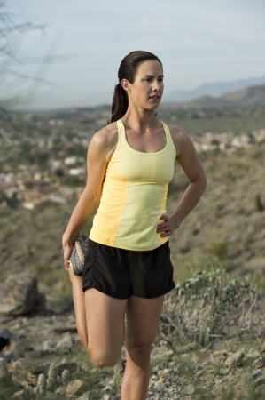 Young woman stretching to warm up for a trail run outdoors at South Mountain Park in Phoenix, Arizona. photo