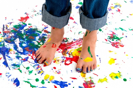 A young girls feet covered in colorful paint on a paint splashed background.  She has her jeans rolled up to avoid the mess.