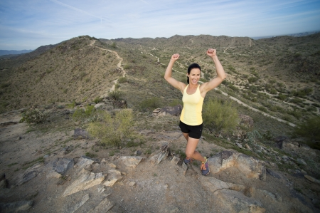 Young woman pauses at the top of a trail midway through her run at South Mountain Park in Phoenix, Arizona. Her arms are outstretched in celebration of making it to the top. photo