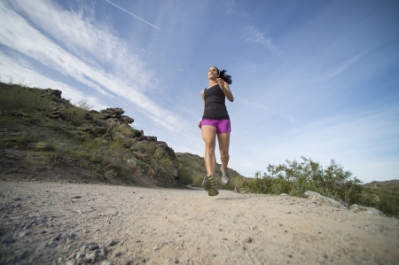 Young woman trail running outdoors at South Mountain Park in Phoenix, Arizona.  Shot from a low angle view. photo