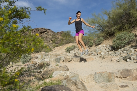 Young woman twisting and jumping over a rock while trail running outdoors at South Mountain Park in Phoenix, Arizona.