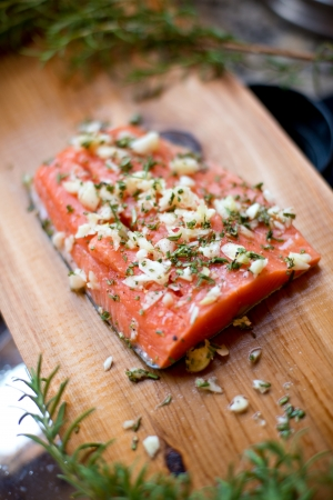 pink salmon: Wild Alaskan salmon fillet on a cedar plank that is ready to be grilled.  Its seasoned with garlic, rosemary, salt and pepper.
