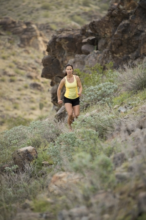 Young woman trail running outdoors at South Mountain Park in Phoenix, Arizona. photo