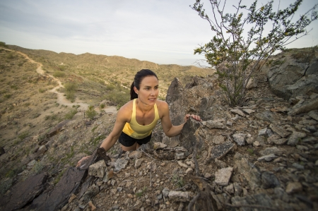 Young woman peaking over some boulders off of a trail at South Mountain Park in Phoenix, Arizona. photo