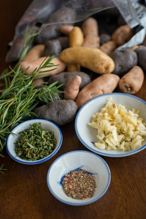 fingerling: Colorful fingerling potatoes spilling out of a bag against fresh rosemary.  There are also 3 bowls filled with fresh minced garlic, pepper and chopped rosemary. Stock Photo