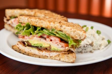 turkey bacon: A deli classic turkey bacon lettuce and tomato sandwich with avocado on whole wheat bread.  Stock Photo