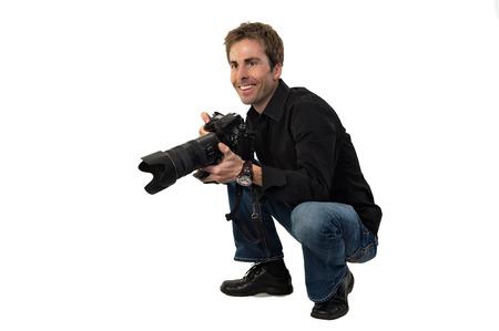 en cuclillas: Retrato de un varón joven fotógrafo con una cámara profesional, agazapado, preparándose para tomar fotos.