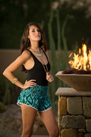 warm up: Beautiful brunette fashion model standing next to a stone column with a fire feature on top posing outdoors.
