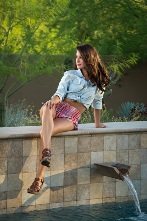 Beautiful brunette fashion model sitting on a stone wall above a pool posing outdoors. photo