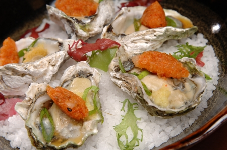 plated: Beautifully plated raw oysters on the half shell over ice.  Each oyster also has a tempura vegetable on top.