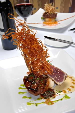 plated: Grilled lamp chop topped with a light sauce and green onions, plated alongside seared ahi tuna over mashed potatoes Stock Photo