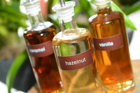 Pretty glass bottles containing hazelnut, vanilla and caramel coffee syrups for flavoring a drink.  Banco de Imagens