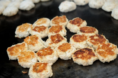 Mini crab cakes cooking on a hot griddle.