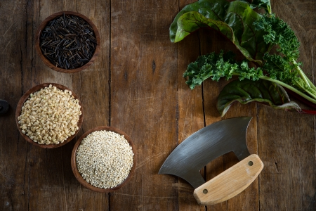 Fun with food, small wood bowls filled with brown rice, quinoa and wild rice on the left.  Kale, Swiss chard and an ulu knife on the right. Copy space dead center. This is shot on a wood table. photo