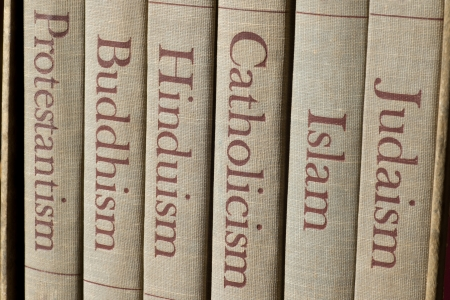 theology: Book spines listing major world religions - Judaism, Islam, Catholicism, Hinduism, Buddhism and Protestantism. Stock Photo