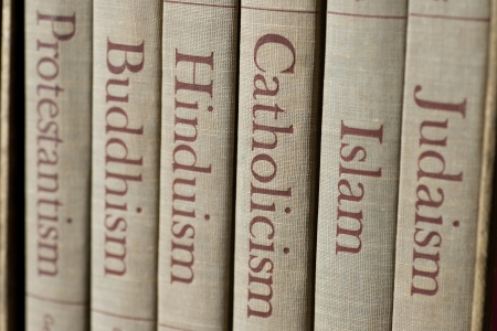 Book spines listing major world religions - Judaism, Islam, Catholicism, Hinduism, Buddhism and Protestantism. The focus is on the word, Catholicism. Stock Photo