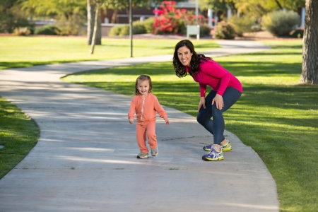 Beautiful young mother and her daughter running in the neighborhood.  They are on a sidewalk in a grassy greenbelt.  The mother is playfully chasing her daughter. photo