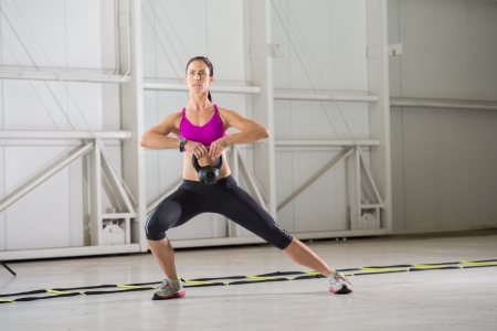 Young brunette woman exercising with a Kettlebell in an indoor urban gym setting.