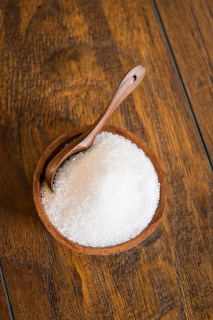 sugar bowl: White sugar in a wooden bowl with a spoon.