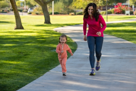Beautiful young mother and her daughter running in the neighborhood.  They are on a sidewalk in a grassy greenbelt.  The mother is playfully chasing her daughter. Imagens