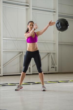 Junge Brünette Frau, die mit einem Medizinball in einer Indoor-Fitness-Studio städtischen Einstellung.