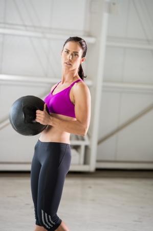 Junge Brünette Frau, die mit einem Medizinball in einer Indoor-Fitness-Studio städtischen Einstellung. Standard-Bild