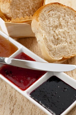 A loaf of fresh baked sliced bread next to a tray of 3 kinds of jams. photo