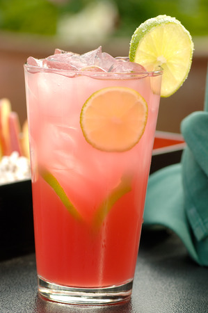 Refreshing cold pink cocktail in a tall glass with lime garnish. Shot on a counter in a bar. Stock Photo