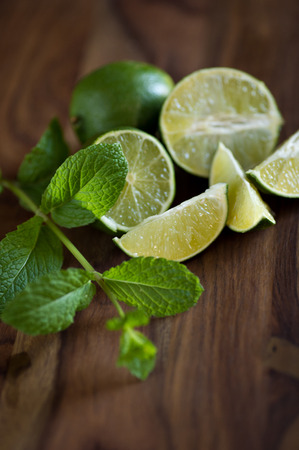 Fresh green limes & fresh mint leaves shot on a wood table. photo
