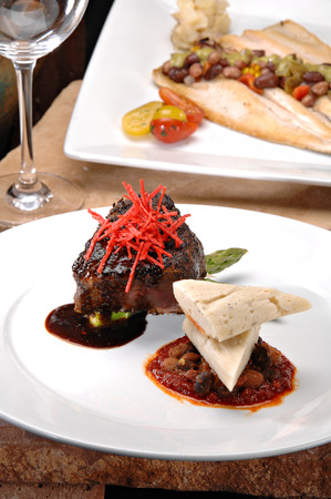 red braised: Braised short ribs on a bright red tomato paste sauce.  Garnished with avacado, sliced tortilla chips and a red wine reduction sauce.  Colorful sauteed spinach is displayed behind the meat.