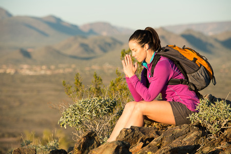 Young woman pauses at the top of a trail midway through her hike at Phoenix Sonoran Preserve in Phoenix, Arizona. She is taking a moment to self reflect. Imagens