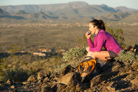 botanas: Mujer joven hace una pausa en la parte superior de una mitad del camino sendero a través de su caminata en Phoenix Sonoran Preserve en Phoenix, Arizona. Ella está teniendo un refrigerio.