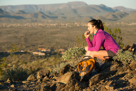 snack: Young woman pauses at the top of a trail midway through her hike at Phoenix Sonoran Preserve in Phoenix, Arizona. She is having a snack.